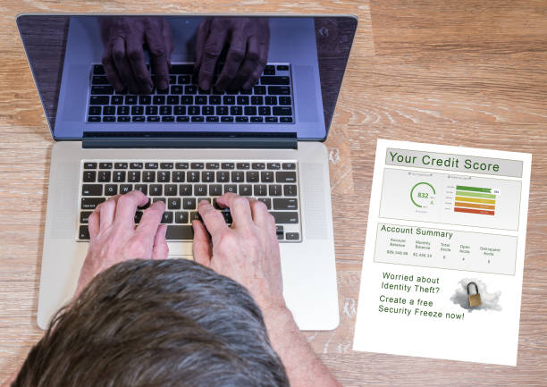 Man typing on laptop with credit report stock photo