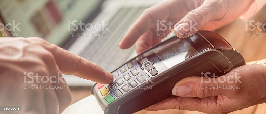 Man typing PIN number in a smart card reader stock photo