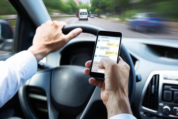 escribir mensaje de texto en el teléfono móvil mientras se conduce el coche del hombre - conducir fotografías e imágenes de stock