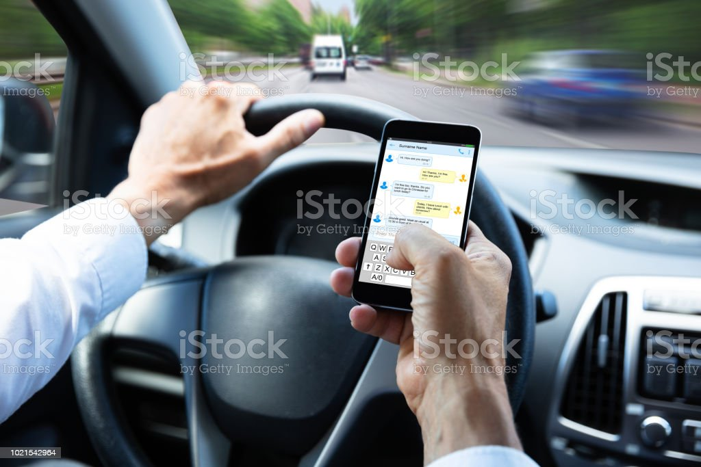 Man Typing Text Message On Mobile Phone While Driving Car stock photo