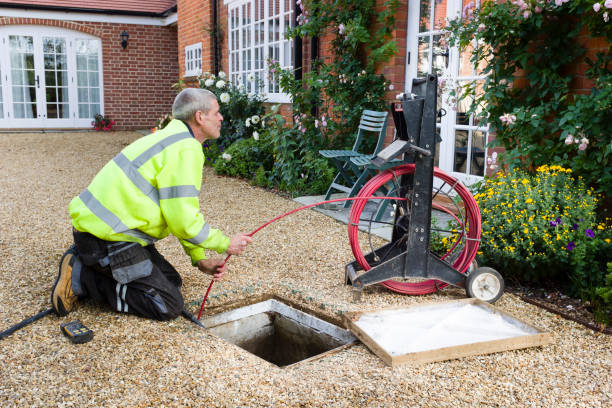 Man unblocking outside drain BUCKINGHAM, UK - October 16, 2019. A professional drain cleaning engineer inspects a blocked household drain sewer stock pictures, royalty-free photos & images