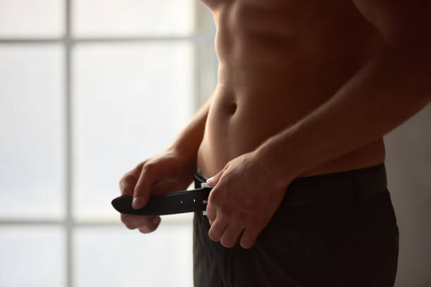 Man unbuckling belt. stock photo