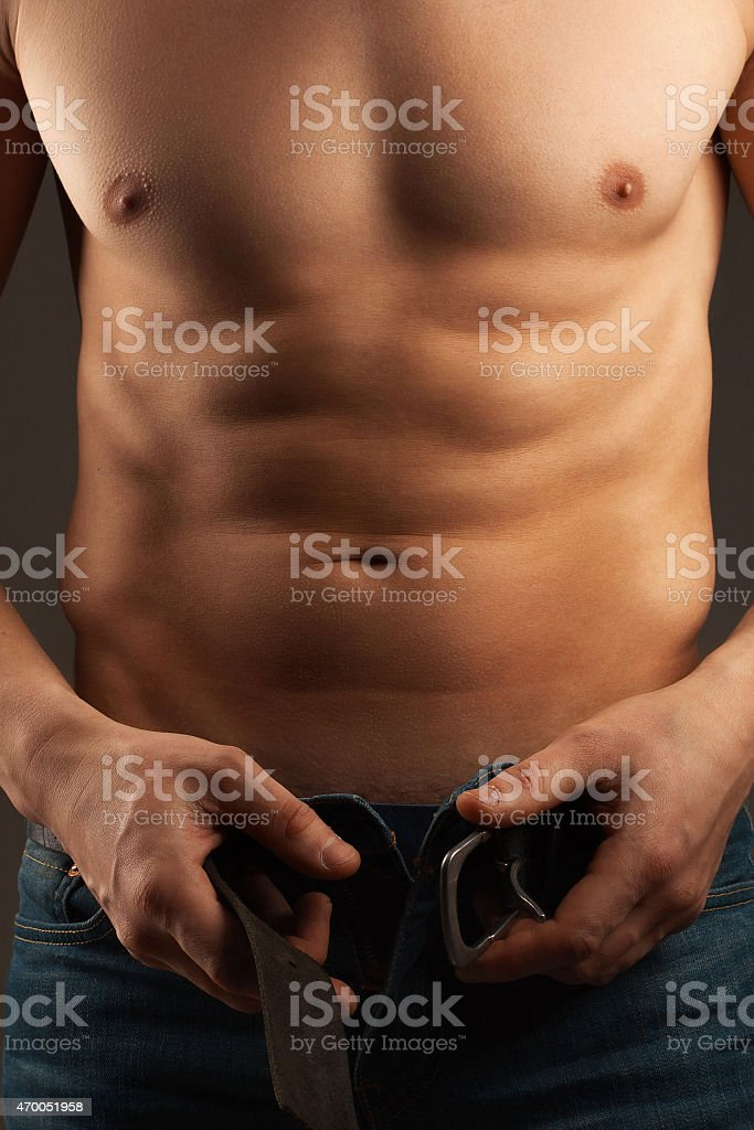 Man unbuckling the belt. Abdominal muscles and chest. stock photo