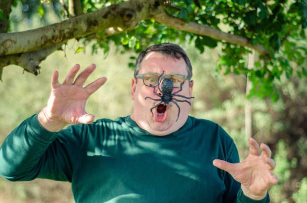 A man under arachnophobia attack stock photo