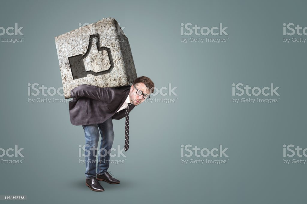 Man bending under a massive stone with a like button on it. Social...