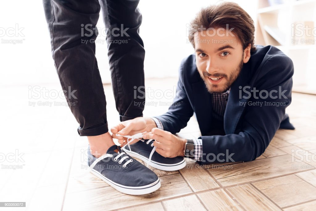 A man under the table to tie laces to his business colleague. stock photo