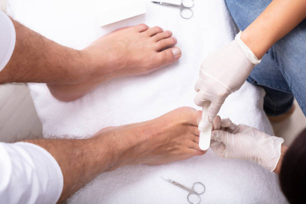 Man Undergoing Pedicure Process In Salon High Angle View Of Beautician Filling Man's Nail In Salon pedicure manicure men beauty spa stock pictures, royalty-free photos & images