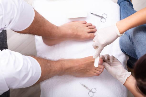 man undergoing pedicure process in salon - pedicure foto e immagini stock