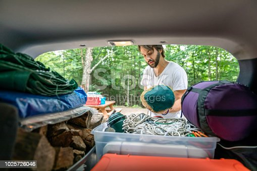 Man Unloading the Car packed with luggage and other items for road trip and Camping