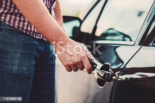 Man unlocking a car door with a key, close up photo. Transportation concept