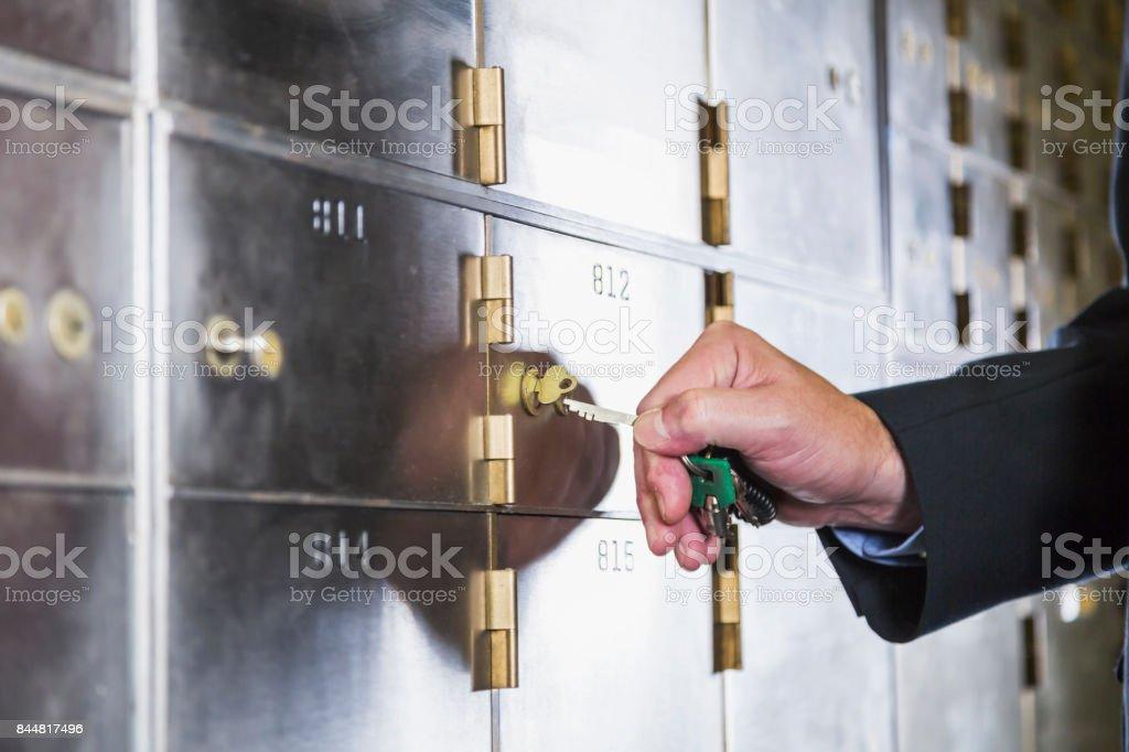 Man unlocking a safety deposit box stock photo