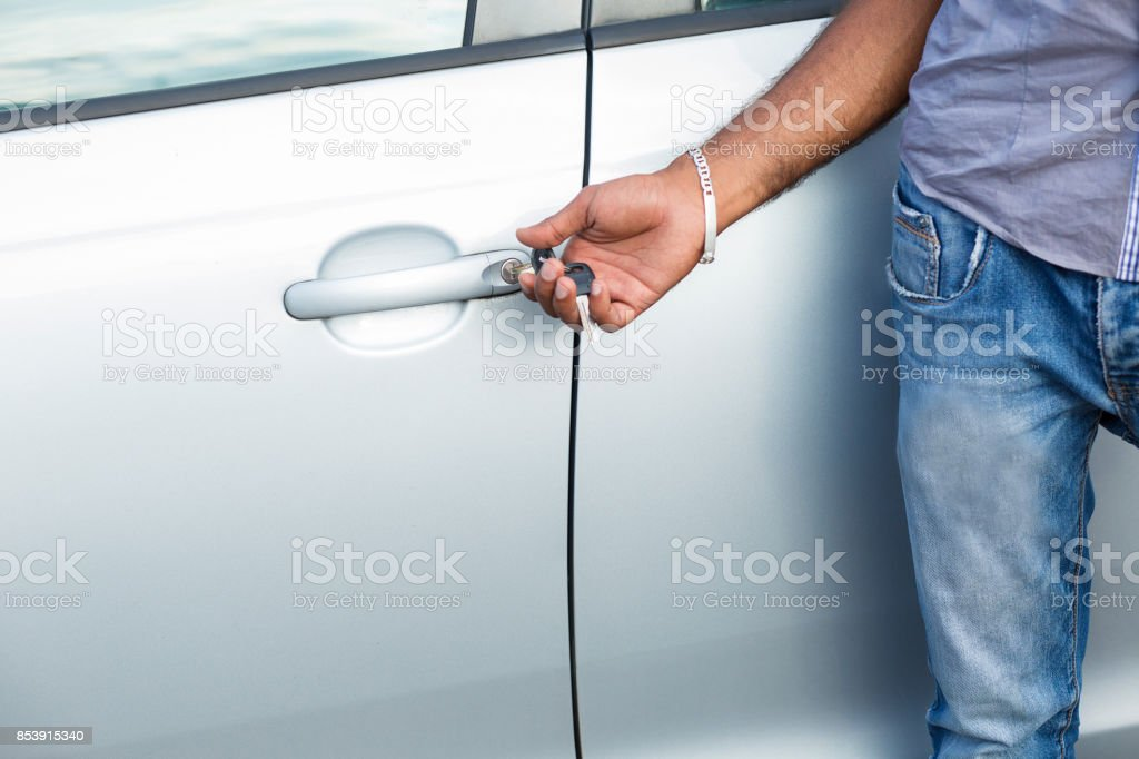 man unlocks car door alarm systems with remote control. Vehicle convenience safety security system stock photo