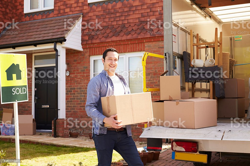 Man Unpacking Moving In Boxes From Removal Truck royalty-free stock photo