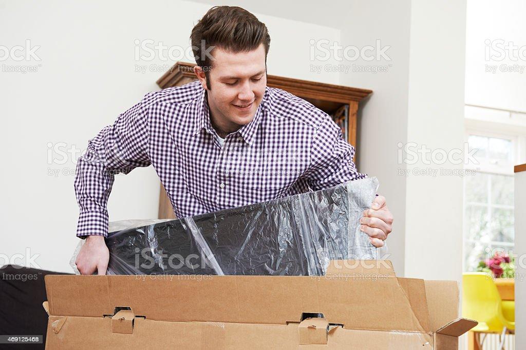 Man Unpacking New Television At Home stock photo