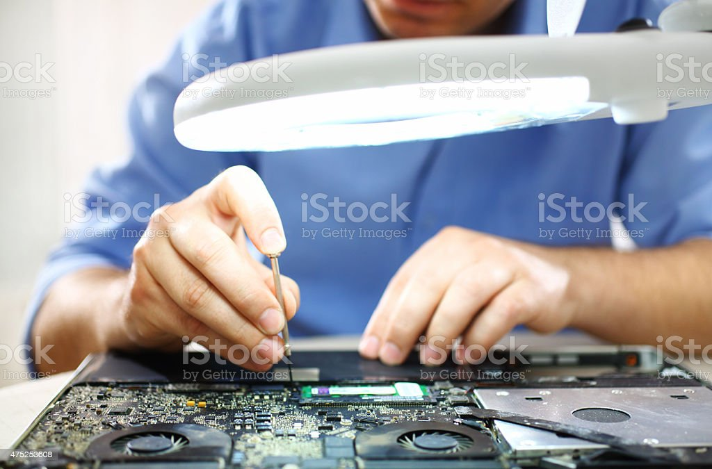 Man unscrewing motherboard of a laptop. stock photo