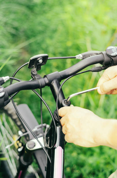 A man unscrews the bolts with a hex wrench on the handlebars of a mountain bike against the background of grass. Repair in the forest road. Close-up stock photo