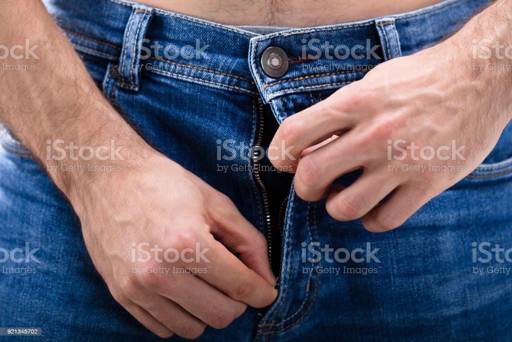 Man openritsen van de spijkerbroek foto