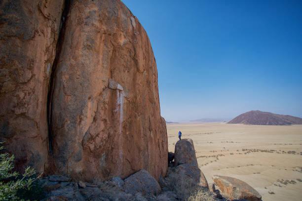mann oben auf einem felsen mit wüstenlandschaft - namib wüste stock-fotos und bilder