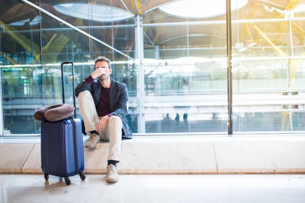 man boos, verdrietig en boos op de luchthaven zijn vlucht is vertraagd - airport pickup stockfoto's en -beelden