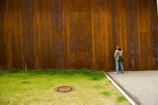 Man Urinating Outside on Rusty Wall Near Green Grass