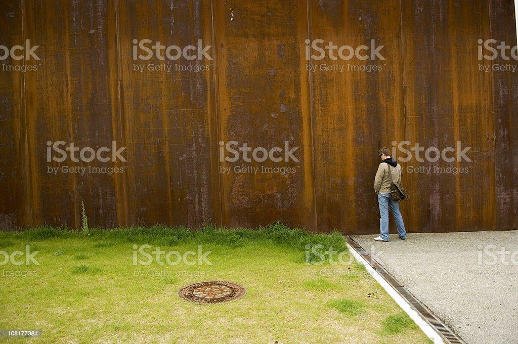 Man Urinating Outside on Rusty Wall Near Green Grass stock photo