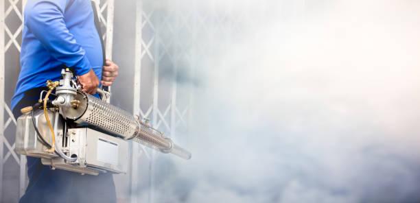 a man use fumigation mosquitoes machine for kill mosquito carrier of zika virus and dengue fever prevention outbreak in school at the rainy season.soft and blur focus. - attrezzatura per la disinfestazione foto e immagini stock