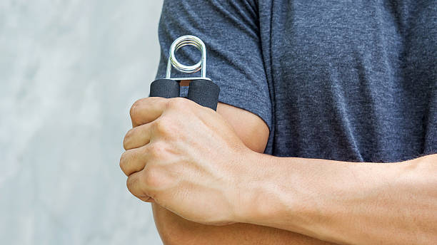 man use handgrips for exercise. - hand grip stock photos and pictures