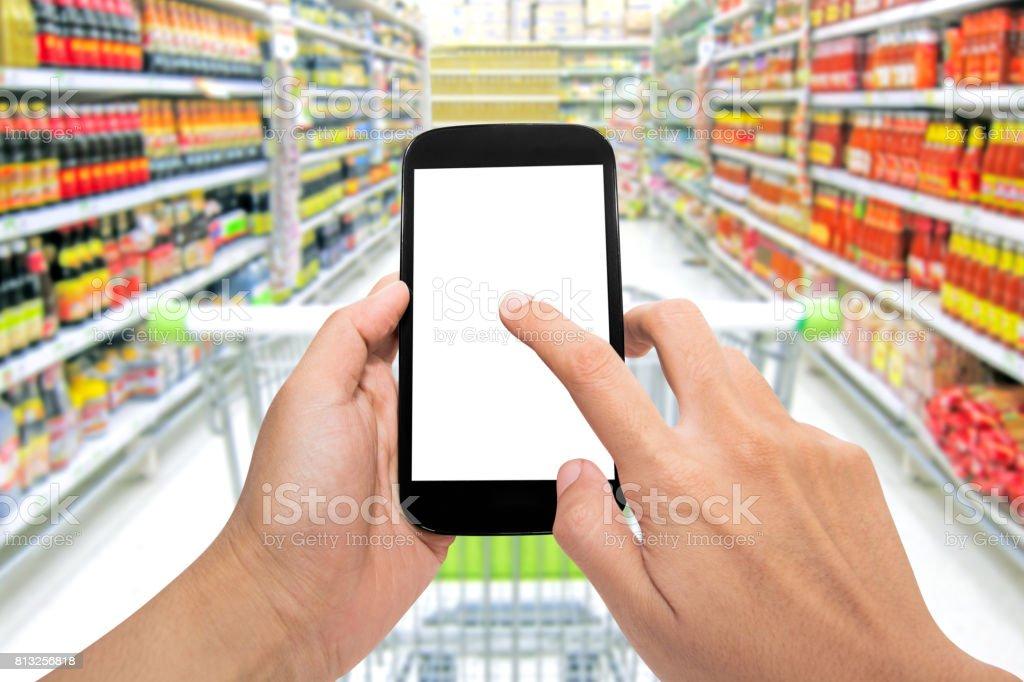 Man use mobile phone, blur image of inside supermarket stock photo