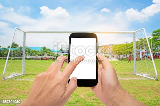 istock Man use mobile with football 667324080