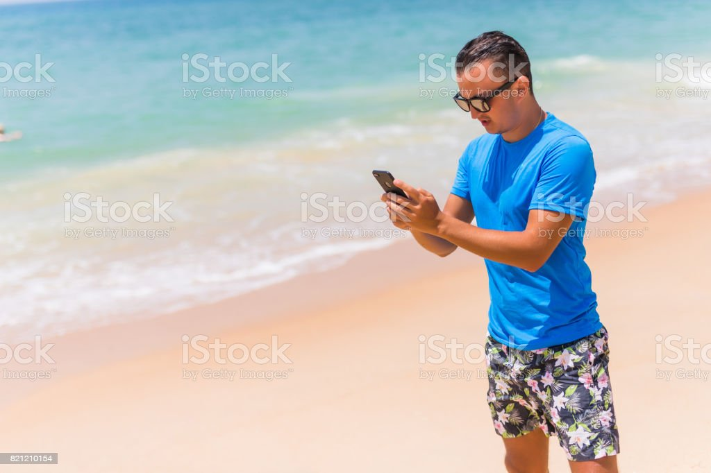 Man use phone on the beach typing or use internet on sunny day stock photo
