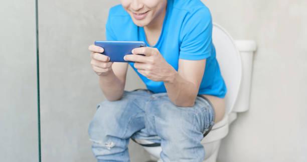 man op toilet telefoon gebruiken - cell phone toilet stockfoto's en -beelden
