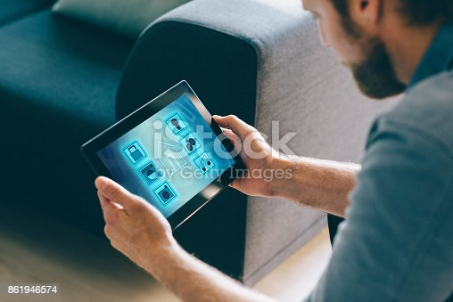 istock Man use smart home automation in living room with digital tablet and mobile app 861946574