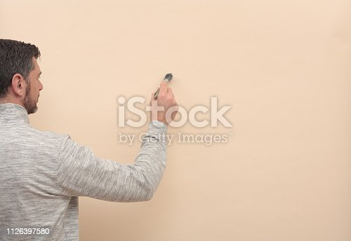 man, dressed with a cotton sweatshirt, uses a paintbrush to write or paint on a blank wall