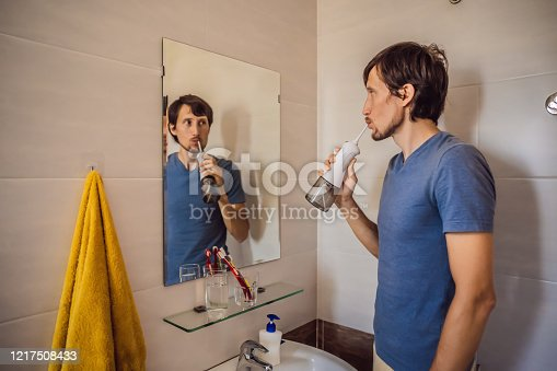 istock A man uses an oral irrigator in his bathroom 1217508433