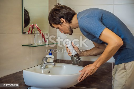 istock A man uses an oral irrigator in his bathroom 1217508439