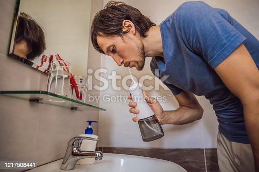 istock A man uses an oral irrigator in his bathroom 1217508441