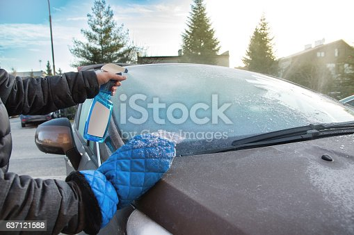 istock Man uses defroster spray to remove frost 637121588
