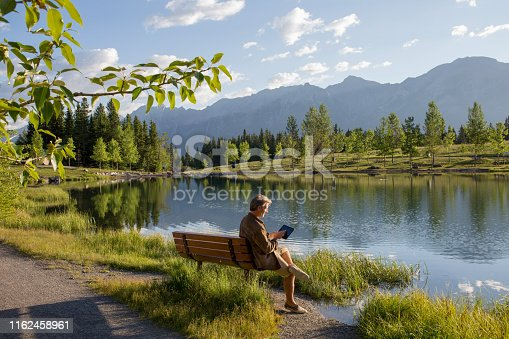 He is sitting on a park bench and surrounded by trees and mountains