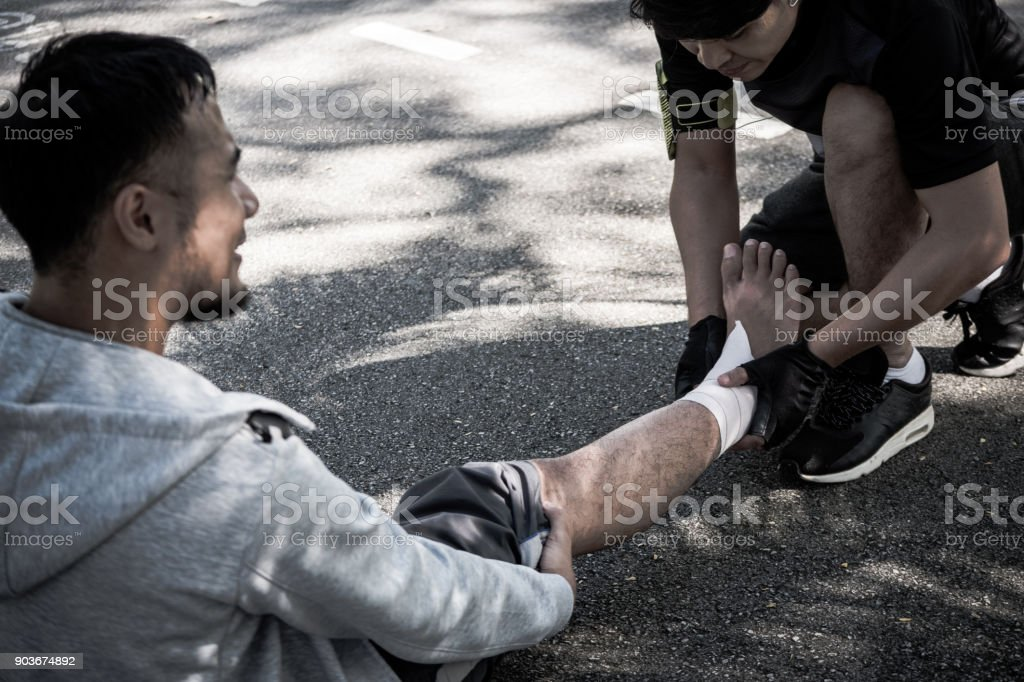 A man uses elastic bandage for pain relief one man's ankle after a workout in a park. stock photo