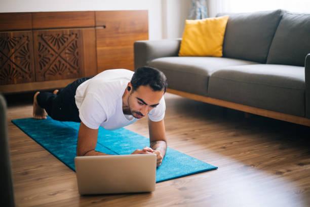 남자는 엎드려 판자 위치에 노트북을 사용 스톡 사진