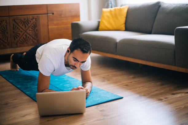 man uses laptop to lean plank position - exercise at home stock pictures, royalty-free photos & images