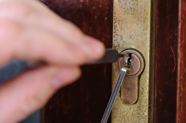 Ein Mann verwendet Lockpicking-Tools, um das Schloss eines Hauses zu wählen. – Foto
