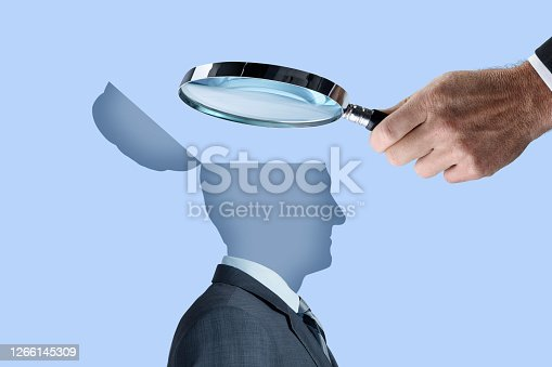 A man uses a magnifying glass to peer into the open mind of a human being.