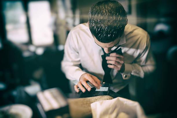 man uses smart phone to learn to tie bow tie - hochzeitsanzug herren stock-fotos und bilder
