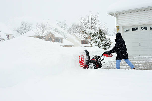 Man uses Snowblower after Blizzard Snow stock photo
