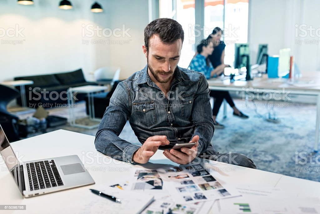 Man using a app mobile phone in modern office start-up. stock photo