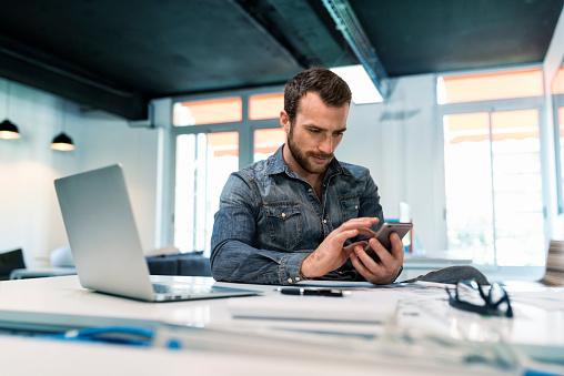 Man Using A App Mobile Phone In Modern Office Startup Foto de stock y más banco de imágenes de 30-39 años
