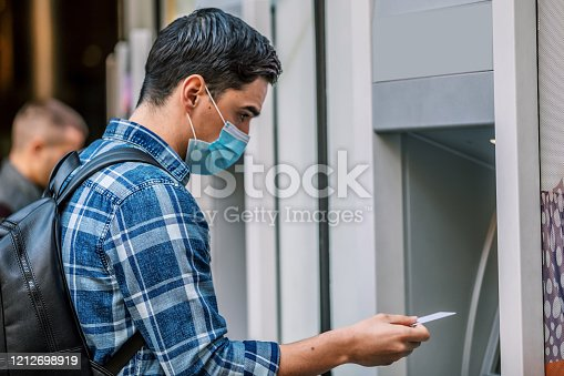 945598452 istock photo Man using a credit card in an atm for cash withdrawal 1212698919