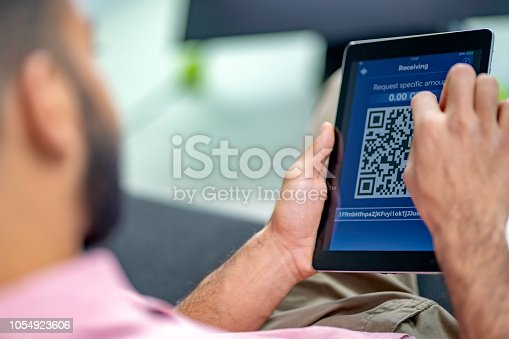 istock Man using a cryptocurrency app to show QR code for receiving funds 1054923606