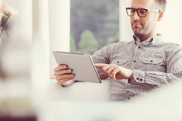 Man using a digital tablet at home stock photo